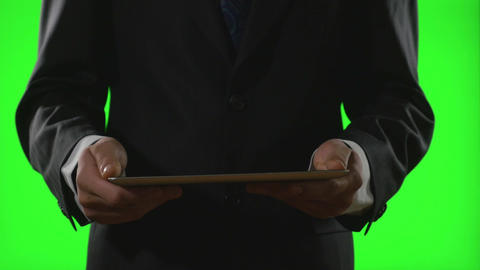 Young businessman using a tablet pc in a virtual business environment on green s Footage