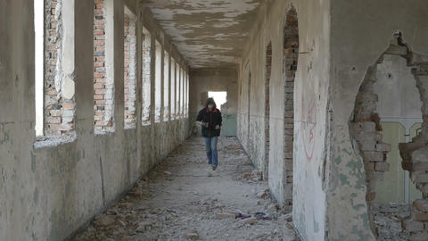 Hooded frightened young man running in an abandoned military building Footage
