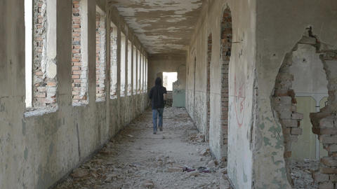 Hooded frightened young man running in an abandoned military building Live Action