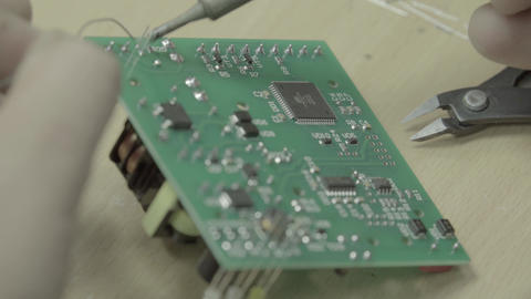 A worker is working on the production of an electronic board. Close-up Live Action