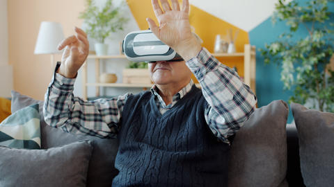 Carefree pensioner using vr glasses at home moving arms sitting on couch in Live Action