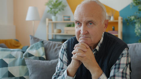 Slow motion of lonely senior man sitting in apartment alone thinking with Live Action