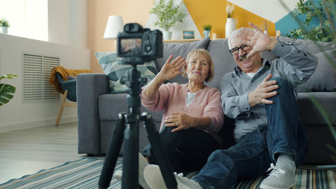 Happy retired couple making video for internet vlog recording with camera at Live Action