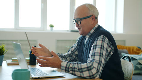 Happy retired man enjoying online communication making video call with laptop Live Action