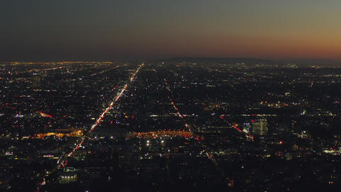 AERIAL: 180 Degree view over Hollywood Hills at Night with view on Downtown Los Live Action