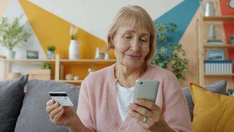 Senior woman shopping online making electronic payment with bank card and Live Action