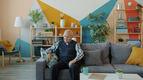 Unhealthy elderly man suffering from back pain standing indoors in apartment Live Action