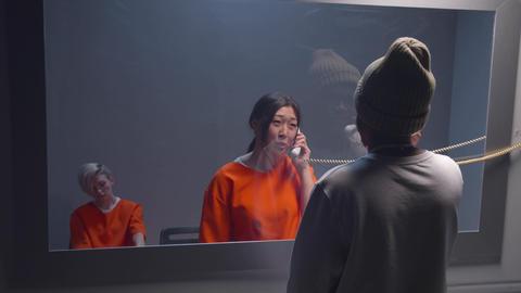 Prisoner talking to man in visit room. Medium shot Live Action