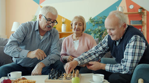 Elderly men playing chess at home while woman drinking tea relaxing at home Live Action