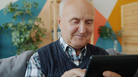 Happy old man enjoying tablet device touching screen smiling relaxing on sofa in Live Action