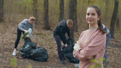Woman and people collecting garbage on background Live Action