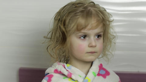 Little girl with wet hair in bathrobe. Mother wipes, dries her daughter's hair Live Action