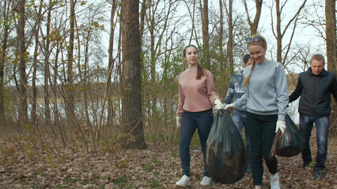 Volunteers with garbage bags walk in the park Live Action