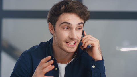 Portrait of positive guy supporting client on phone. Man making winner gesture Live Action
