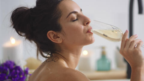 Relaxed woman drinking champagne at bath. Sexy girl relaxing with glass of wine Live Action