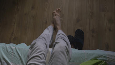 High angle view of a handsome man waking up and putting on slippers Footage