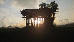 Sun silhouette of farmer's shack in stubble burning rice fields in Ubud Bali Footage