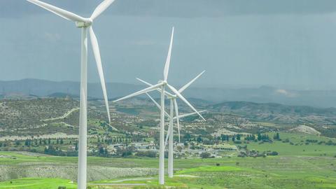 Wind farm in rural area. Wind turbines in green field rotating under stormy sky Footage