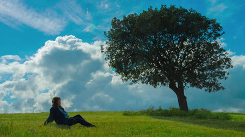 Young woman enjoying solitude under green tree. Relaxation alone with nature Footage