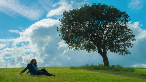 Beautiful brunette female under tree, upset woman sitting alone on green grass Footage