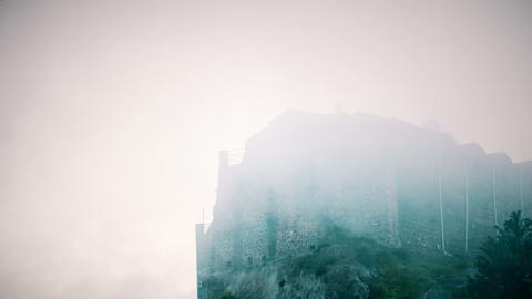 Terrible medieval building with stone walls hidden in fog. Mystical atmosphere Footage