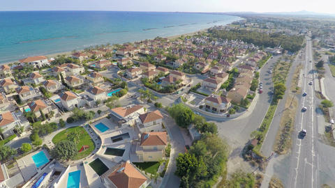 Aerial shot of luxury cottages along coastline. Top view of beautiful seascape Footage