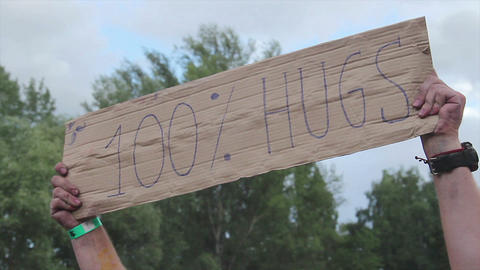 Hands holding free hugs sign up in air. Friends having fun, positive emotions Live Action