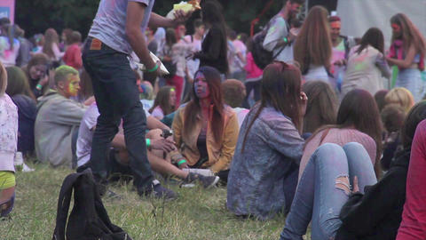Happy young people at open air festival sitting on grass having snacks, chatting Footage
