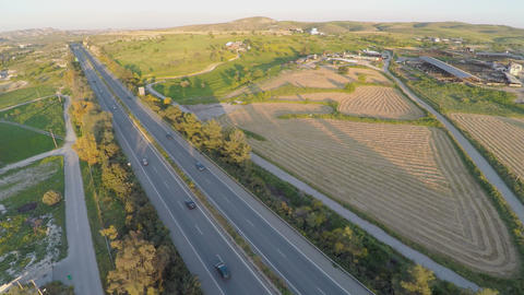 Aerial shot of many trees, harvested farming fields, green hills along highway Footage