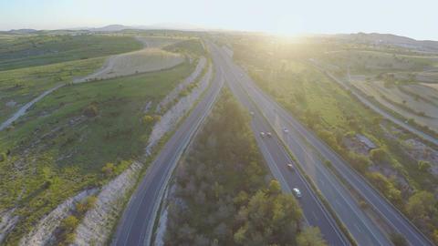 Vehicles moving on interstate highway. Beautiful sunset on horizon. Aerial shot Footage