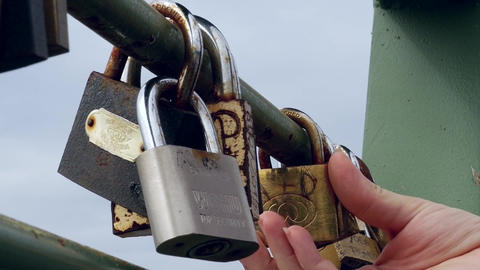 Hand woman studying metal padlock attached to love on the iron railing of a brid Footage