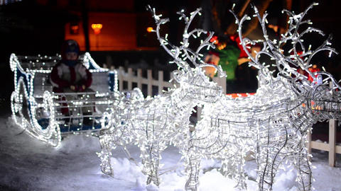 Small boy sitting in a sleigh adorned with white lights and pulled by four reind Footage
