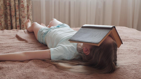 Face sleeping girl covered opened book in home bedroom. Young girl lying on bed GIF