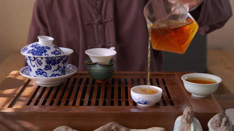 Male hand pouring hot red tea from glass pot in bowl on traditional ceremony Live Action