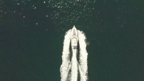 Luxury motorboat yacht traveling through ocean, aerial birds eye view follow Live Action
