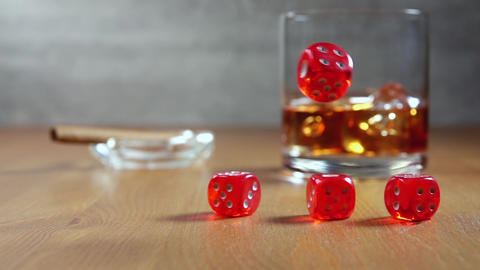 Whiskey and Dice on a Wooden Table. Slow Motion Live Action