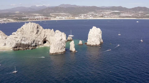 Aerial of The Aerial in Cabo San Lucas yachts sailing around landmark scenery Live Action