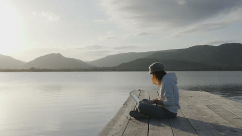 Internet freelance job choice concept: a young woman works on her laptop sitting on a pier by a lake Live Action