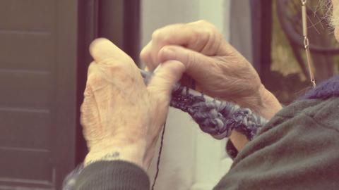 closeup on old lady hands to knitting in a terrace Live Action