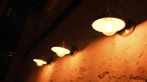 Lamps on the wall in a bar. Classic wall lamps with a shade. Cozy darkened Live Action
