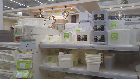 Plastic dishes and containers on a shelf in a hardware store Live Action