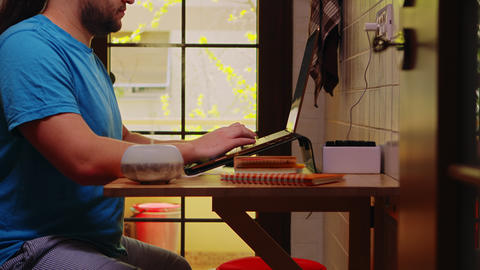 Bearded freelancer working on laptop from home Live Action