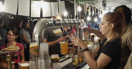 Bartenders pouring draught beer during street festival Live Action