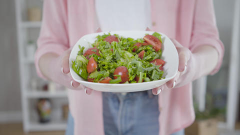 Unrecognizable Caucasian woman showing fresh tasty salad at camera. Female hands Live Action