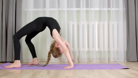 Young girl training gymnastic bridge on carpet at home. Gymnast girl walking Live Action