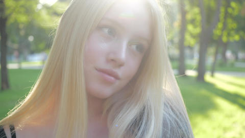 Attractive European blonde teen girl with natural make-up walks in nature on a Live Action