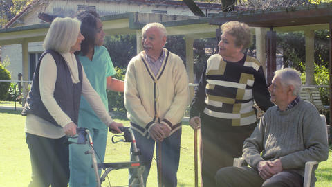 Elderly people telling stories outdoor, african nurse happy with them Live Action