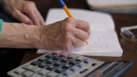 Woman counts on a calculator and writes in a notebook Live Action