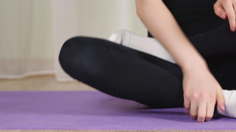Woman sitting in lotus pose on home yoga training. Female zen fingers and legs Live Action