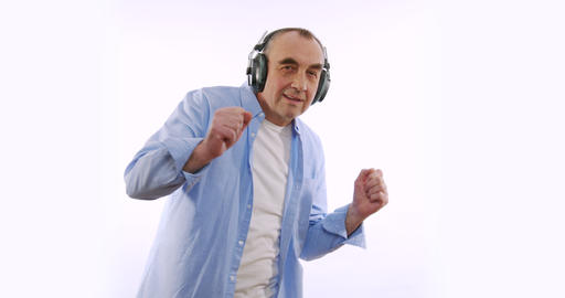Slow motion of happy enderly man in wireless headphones dancing enjoying music Live Action